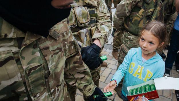 Ein ukrainischer Soldat mit Skimaske erhält von einem kleinen Mädchen ein Geschenk.