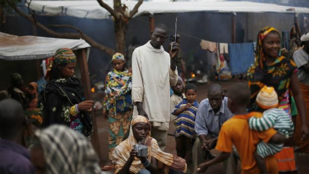 Ein Mann hält sich ein portables Radio ins Ohr in einem Flüchtlingscamp.