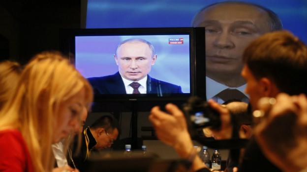 Russische Journalisten schauen sich eine Rede Putins im Fernsehen an.