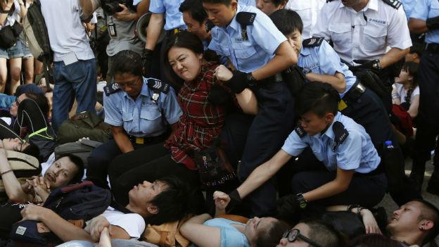 Demonstrierende eines Sitzstreiks werden von Polizisten weggetragen