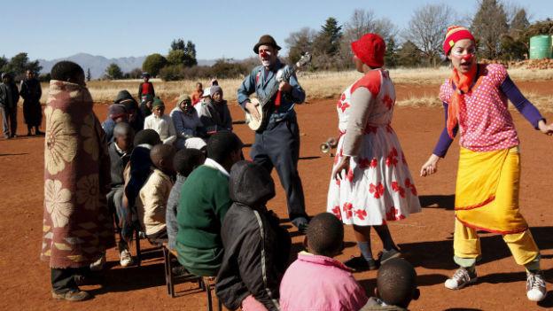 Clowns spassen mit Kindern in einer kargen Wüstenlandschaft.