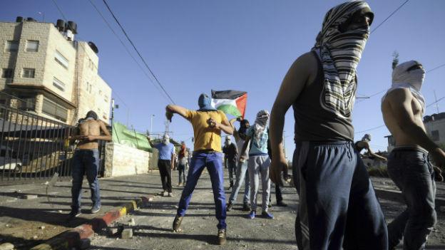 Palästinenser in Jerusalem schiessen Steine bei Zusammenstössen mit der israelischen Armee.
