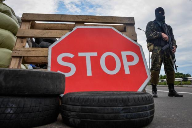 Grosses Stoppschild und Autoreifen, im Hintergrund ein bewaffneter Mann im Tarnanzug.