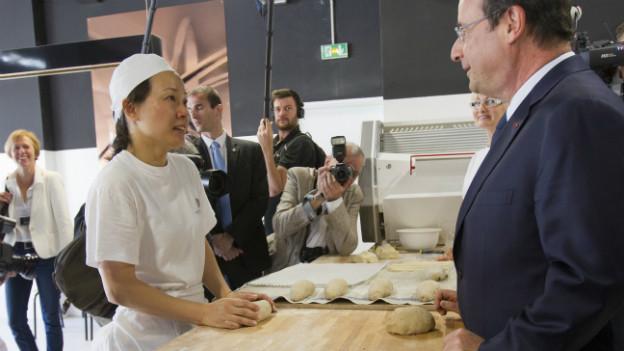 Frankreichs Präsident Hollande lässt sich die Arbeit in einer Bäckerei erklären.