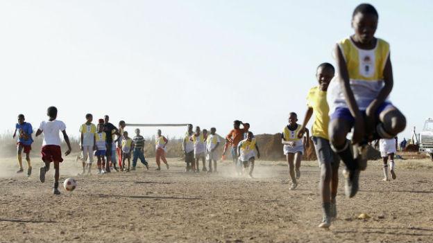 Jugendliche und Kinder spielen Fussball in Südafrika.