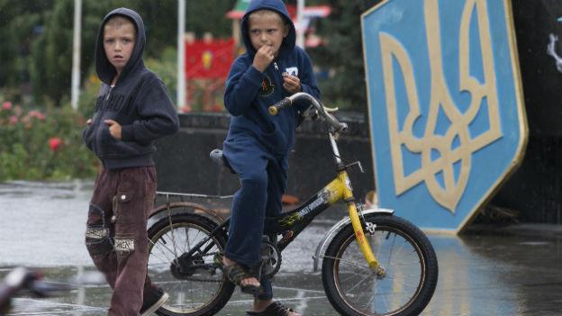 Zwei Jungen, einer mit Fahrrad, stehen vor einem Schild mit dem ukrainischen Emblem.