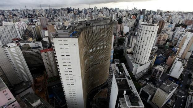 Aufnahme des Edificio Copàn in Sao Paulo, dem höchsten Gebäude in Südamerika. Es ist grau, etwas schmuddelig und steht an einem Ort, der ohnehin schon sehr dicht bebaut ist.