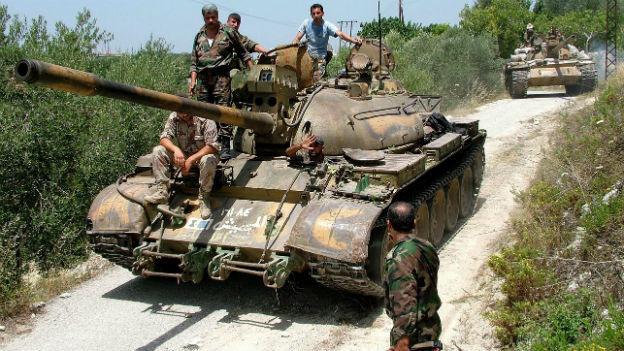 Ein Panzer auf einer Landstrasse mit mehreren bewaffneten Soldaten, die auf dem Panzer stehen oder sitzen