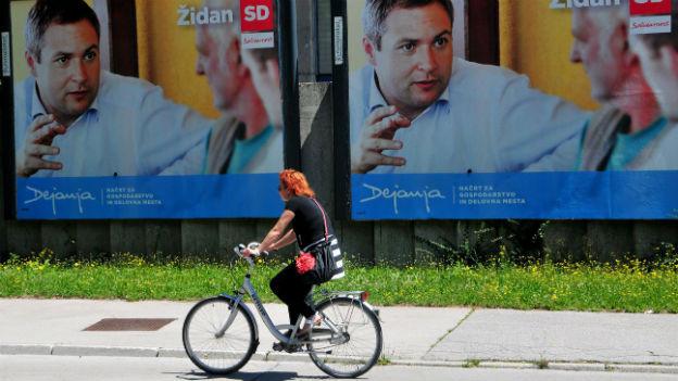 Eine Velofahrerin fährt auf der Strasse an zwei Wahlplakaten vorbei.