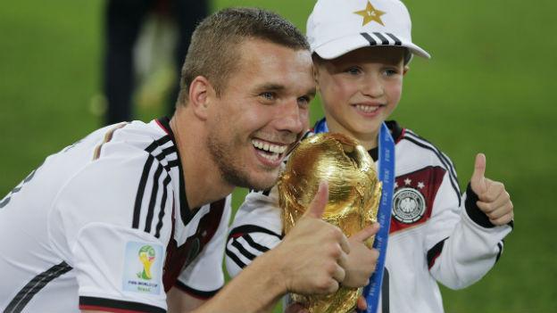 Lukas Podolski und sein Sohn mit dem Fussball-WM-Pokal.