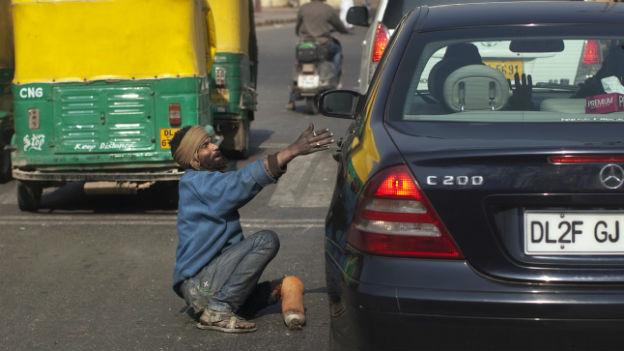 Bettler in einer Strasse in Delhi vor einem Auto.