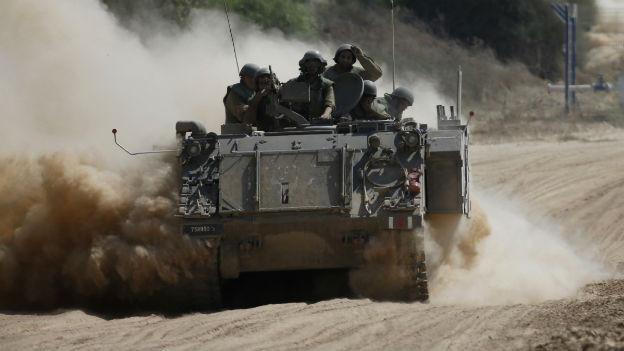 Ein israelischer Panzer rollt auf einer Sandstrasse.