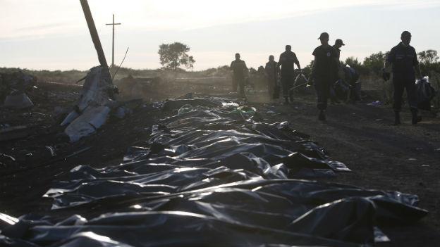 Verhüllte Leichen im Vordergrund, im Hintergrund Ukrainische Rettungskräfte.