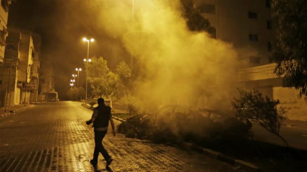 Ein Palästinenser läuft nach einem Luftbeschuss an einem Autowrack vorbei.