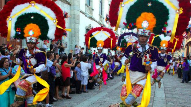 Indigene Tänzer in farbenfrohen Gewändern in den Strassen Oaxacas.