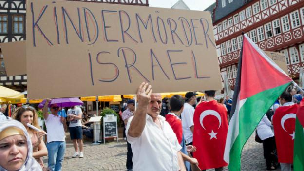 Ein Mann hält an einer Demonstration in Frankfurt am Main ein Schild mit der Aufschrift «Kindermörder Israel» in die Höhe.
