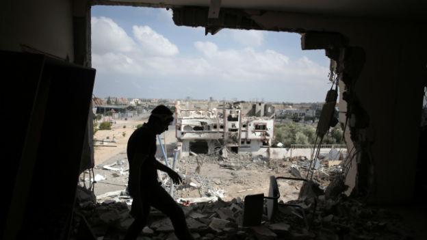 Ein Mann steht in einem zerstörten Gebäude im Gazastreifen.