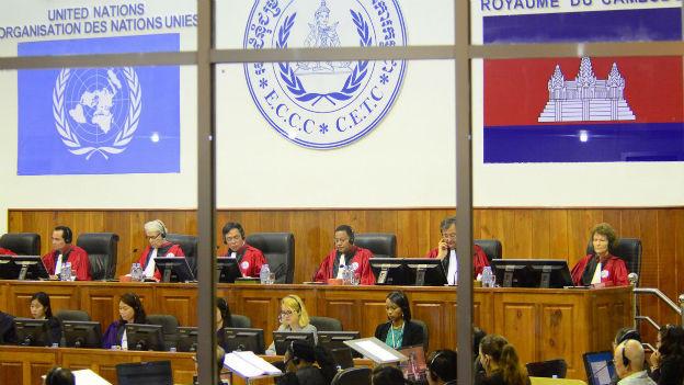 Blick ins Völkermordtribunal, zu sehen sind Richter in roten Roben und weitere Gerichtsmitarbeitende, dahinter das Emblem der UNO und das Wappen von Kambodscha