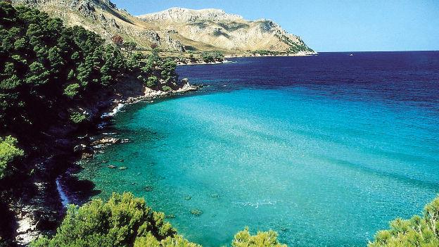 Eine türkisblaue Bucht auf Mallorca, im Hintergrund ein Bergrücken.