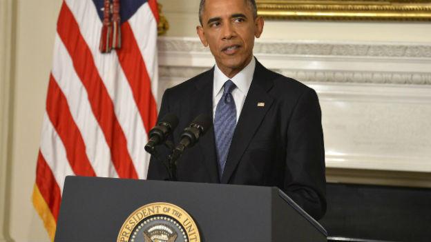US Präsident Obama steh vor US Flagge.