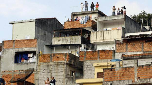 Menschen stehen auf den Dächern ihrer Häuser in Sao Paolo (Archivbild).