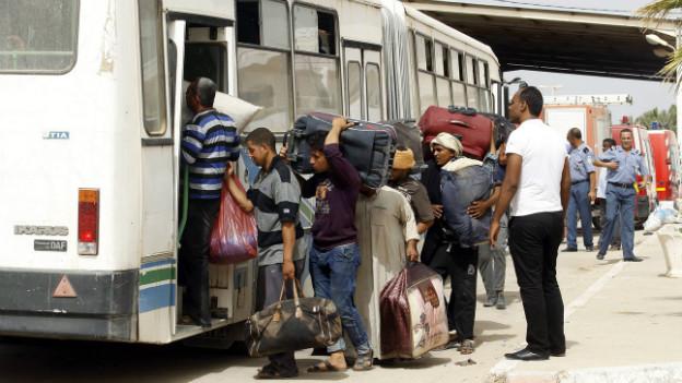 Lybische Flüchtlinge besteigen einen Bus in Ben Ghardane in Tunesien.