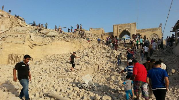 Menschen inspizieren die Trümmer des zerstörten Grabes des Propheten Jonah in Mosul.
