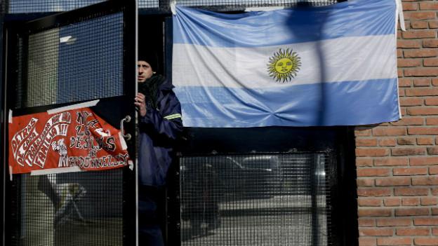 Ein Mann öffnet eine Türe, an der eine argentinische Flagge hängt.