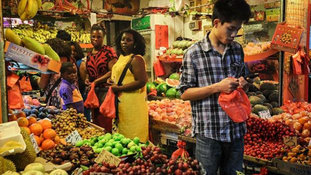 Chinese und Frauen aus Afrika in einem Lebensmittelgeschäft.