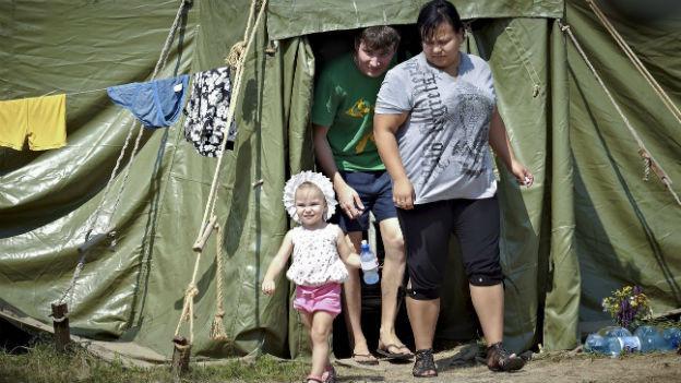 Eine Frau, ein Junge und ein kleines Mädchen vor einem Zelt in einem Flüchtlingslager in der Nähe der Grossstadt Lugansk.