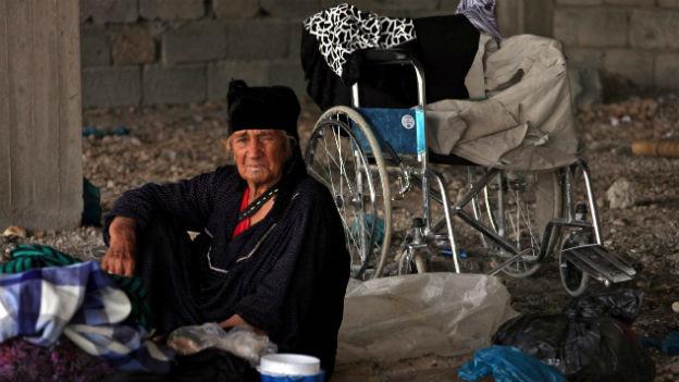 Eine ältere Frau sitzt auf einer Decke am Boden in einer Bauruine, im Hintergrund steht ein Rollstuhl.