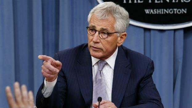 Chuck Hagel sitzt an einem Tisch vor einem Pentagon Schild und zeigt mit dem Zeigefinger auf jemanden.