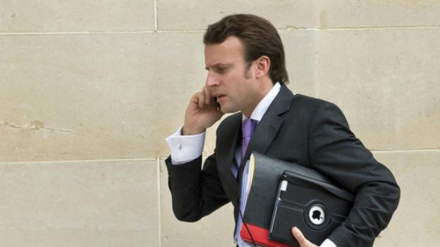 Macron am Handy mit Akten unter dem Arm geht an Mauer vorbei