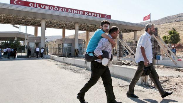 Ein verletzter Flüchtling aus Syrien passiert die türkische Grenze.