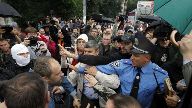 Eine Menschenmenge umringt einen Polizisten in Kiew.