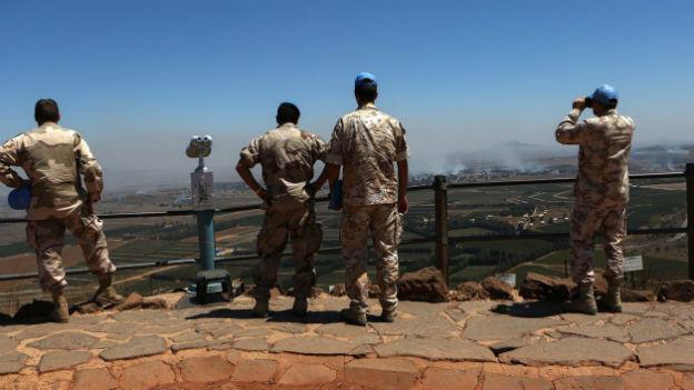 4 Blauhelmsoldaten stehen an einer Brüstung auf einem Hügel und blicken ins Land; weiter hinten steigt Rauch auf