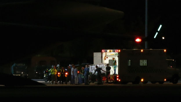 Es ist Nacht, ein Krankenwagen steht vor einem grossen Transportflugzeug.