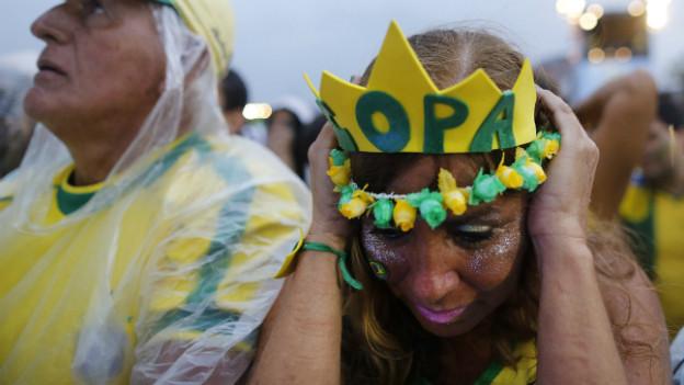 Nach dem verlorenen Halbfinal sind die brasilianischen Fans bestürzt - eine Frau hält den Kopf zwischen ihren Händen.