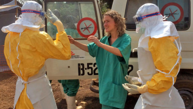 Drei Mitarbeitende von Ärtze ohne Grenzen stehen vor einem Fahrzeug, zwei davon in Schutzanzügen.