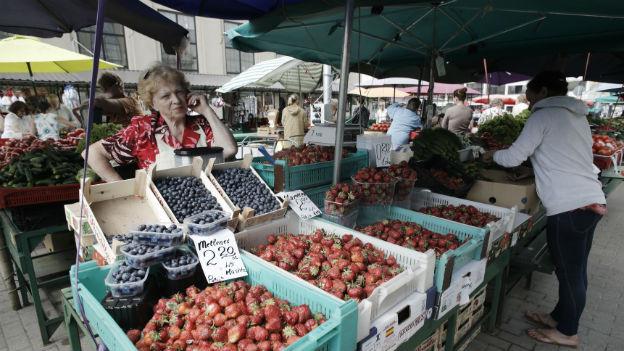 Eine Marktfrau telefoniert hinter einem Marktstand mit vielen Früchten und Gemüse.