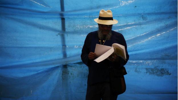 Ein Mann steht vor einer blauen Wand und blättert in einem Jahresbericht von Amnesty International.