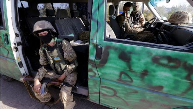 Ein ukrainischer Soldat sitzt in der Türöffnung eines Militärautos und macht Pause.