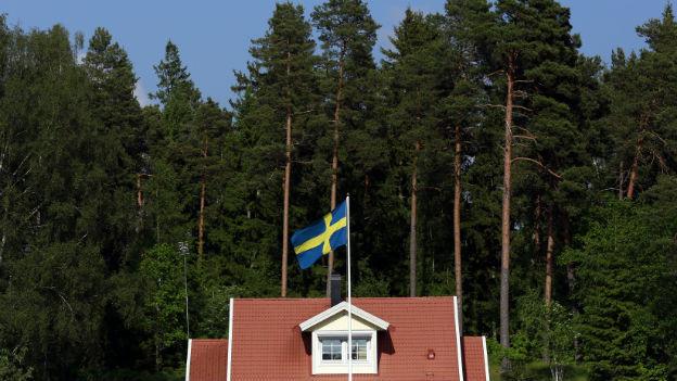 Ein typisch rotes Schweden-Haus mit einer schwedischen Flagge vor einem Wald