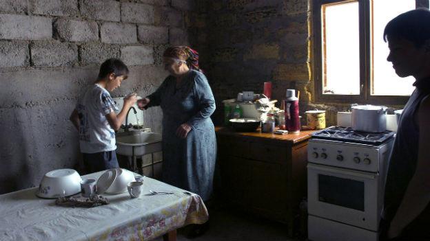 Die Küche einer ukrainischen Familie, Wasser läuft aus dem Wasserhahn, die Wände sind unverputzt, drei Menschen sind am Kochen.
