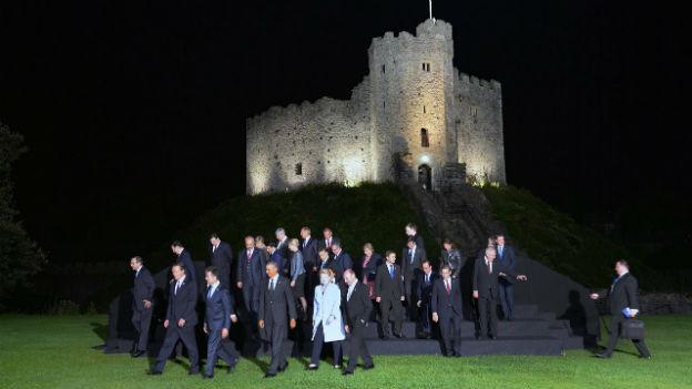 Staats- und Regierungschefs der NATO-Länder steigen von einem schwarzen Treppchen herunter nach einem Fototermin. Im Hintergrund das Schloss Cardiff.