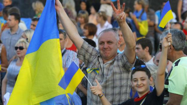 Mann und Bub an Demo mit ukrainischer Flagge lächeln und machen Victory-Zeichen