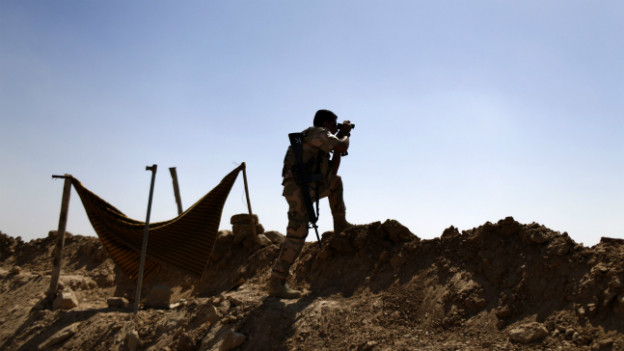 Ein Peschmerga sucht mit einem Feldstecher nach IS-Truppen in der Nähe von Makhmour.