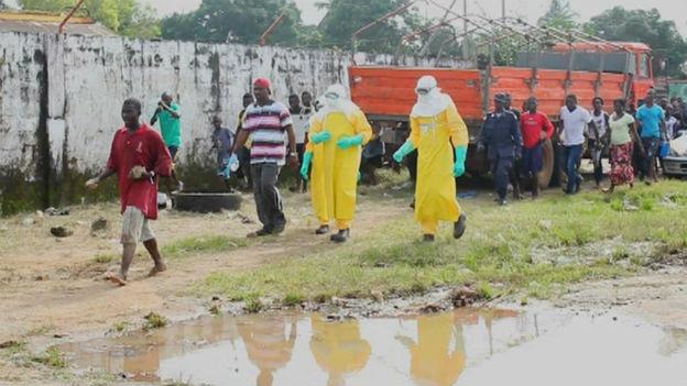 Strassenszene: Gesundheitspersonal und eine Gruppe von Menschen in Liberia