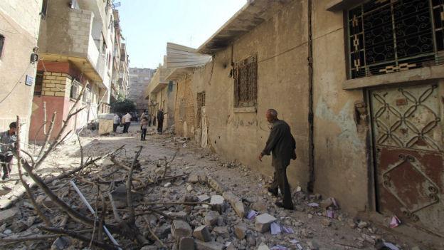 Eine Altstadt-Gasse in Damaskus, ein Schutthügel liegt im Vordergrund, ein Mann blickt ihn an beim Vorbeilaufen