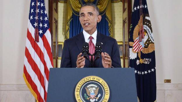 US-Präsident Obama steht hinter dem Rednerpult im Weissen Haus, dahinter sichtbar die US-Flagge.